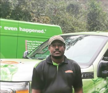 male employee standing in front of company truck