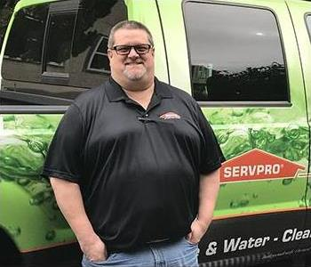 male employee standing in front of a SERVPRO truck