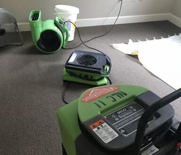 Room with SERVPRO equipment on a carpeted floor